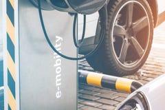 Ravitaillement d'automobile pour l'e-mobilité de voitures électriques dans la voiture de fond, roue Photo stock