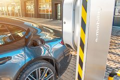 Ravitaillement d'automobile pour l'e-mobilité de voitures électriques dans l'e-voiture de fond, roue L'e-voiture de remplissage,  Photos libres de droits