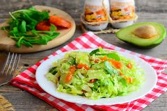 Raw сabbage avocado salad. Easy fresh cabbage salad with avocado, dried apricots, ruccola and sesame on a plate Stock Photos