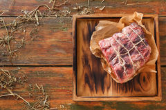 Raw aged prime black angus beef in craft papper on rustic wood Stock Images