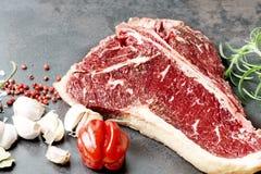 Raw aged steak and seasoning on dark background Stock Photo