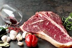 Raw aged steak and seasoning on dark background Stock Images