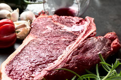 Raw aged steak and seasoning on dark background Royalty Free Stock Image