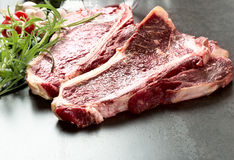 Raw aged steak and seasoning on dark background Stock Image