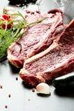 Raw aged steak and seasoning on dark background Royalty Free Stock Photos
