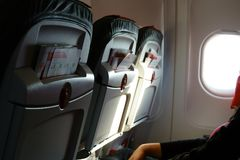 Raw airplane seats with advertising booklets in aircraft passenger cabin. Light from porthole. People in chair.  Royalty Free Stock Images