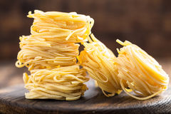 Raw all`uovo pasta, egg noodles on dark wooden rustic background Stock Images