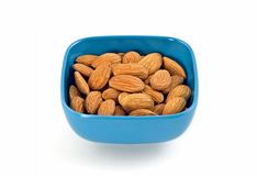 Raw almonds. Raw whole almonds in blue plastic dish isolated on white background Royalty Free Stock Image