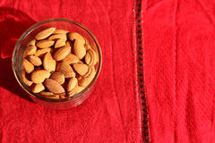 Raw almonds. Isolated on the red background in glass bowl Royalty Free Stock Image