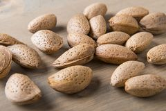 Almonds on wooden table. Raw almonds, with skin and rind on wooden background royalty free stock photo