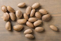 Almonds on wooden table. Raw almonds, with skin and rind on wooden background stock image