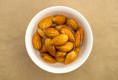 Raw almonds soaking in a white bowl of water Royalty Free Stock Image