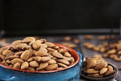 Raw Almonds. Whole almonds in bowl and wooden spoon against a rustic background Stock Photo