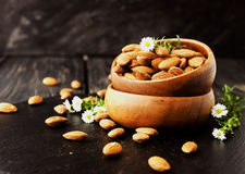 Raw almonds on wooden bowl, selective focus, space for text Royalty Free Stock Photography