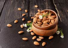 Raw almonds on wooden bowl, selective focus, space for text Royalty Free Stock Photos