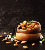 Raw almonds in a wooden bowl selective focus Stock Photos