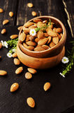 Raw almonds in a wooden bowl selective focus Stock Image