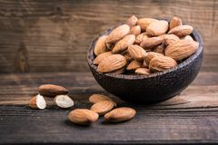 Raw almonds. In wooden bowl on wood royalty free stock photos