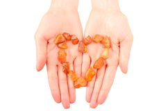 Raw amber shaped heart on hand of woman Royalty Free Stock Photo