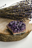 Raw amethyst rock with bunch of aromatic lavender flowers on natural wood rustic esoteric. Raw amethyst rock with bunch of aromatic lavender flowers on natural Stock Photo