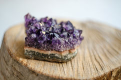 Raw amethyst rock with reflection on natural wood Royalty Free Stock Image