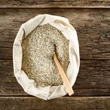Raw Arborio Risotto Rice. Raw arborio risotto short-grain rice in bag with wooden spoon, photographed overhead on wood Selective Focus, Focus on the rice stock images