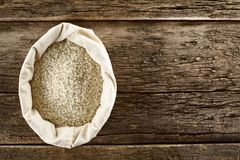 Raw Arborio Risotto Rice. Raw arborio risotto short-grain rice in bag, photographed overhead on wood Selective Focus, Focus on the rice Royalty Free Stock Photography