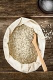 Raw Arborio Risotto Rice. Raw arborio risotto short-grain rice in bag with wooden spoon, sea salt on the side, photographed overhead on wood Selective Focus Stock Images