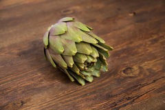 Raw Artichoke. On dark wood Stock Photos