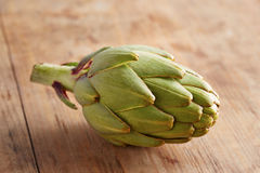 Raw artichoke on wooden table Stock Photography