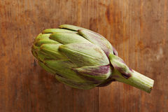 Raw artichoke on wooden table Royalty Free Stock Image