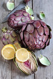 Raw artichokes. Raw purple artichokes with lemon. Selective focus Royalty Free Stock Photos