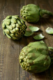 Raw artichokes on a wooden surface. Closeup of some raw artichokes on a dark wooden surface Royalty Free Stock Image