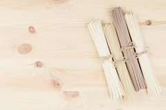 Raw asian noodles close up on beige wooden board background, top view. Stock Image