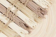 Raw asian noodles close up on beige wooden board background, top view. Royalty Free Stock Photo
