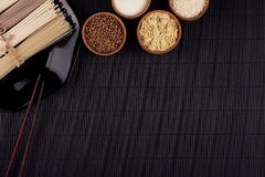 Raw asian noodles with ingredient in wooden bowls on black striped mat background with copy space. Royalty Free Stock Photos
