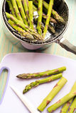 Raw asparagus in saucepan and on cutting board Royalty Free Stock Photo
