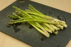 Raw asparagus spears. Bunch of freshly rinsed whole raw asparagus spears on black cutting board royalty free stock images
