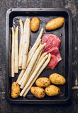 Raw asparagus with veal meat schnitzel and yong potatoes on black backing tray Stock Photo