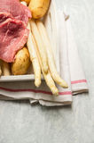 Raw asparagus with veal schnitzel and fresh potatoes. On rustic background Royalty Free Stock Images