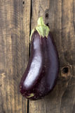 Raw aubergines or eggplants on wooden backround. Royalty Free Stock Image