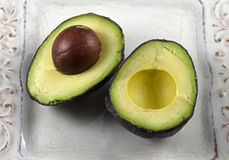 Raw avocado halves. Close-up on raw avocado halves on a white dish Royalty Free Stock Image