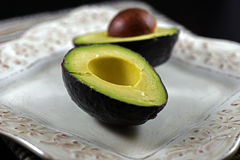 Raw avocado halves. Close-up on raw avocado halves on a white dish Royalty Free Stock Photos