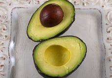 Raw avocado halves. Close-up on raw avocado halves on a white dish Stock Photography