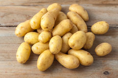 Raw baby potatos. On rustic wooden background Royalty Free Stock Photo