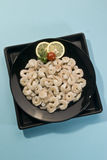 Raw baby shrimps with lemon and tomato on black plate on blue background Stock Photography