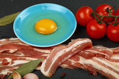 Raw bacon slices, egg yolk, tomato on black board. Raw pork bacon slices, rashers, egg yolk in blue saucer, spices, peppercorns and red fresh cherry tomatoes on Stock Image