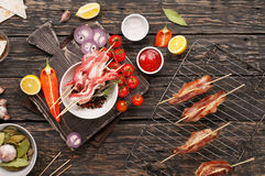 Raw bacon slices with ready grilled bacon and vegetables Royalty Free Stock Photo