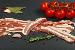 Raw bacon slices, spice and tomato on black board. Raw pork bacon slices, rashers, spices, peppercorns, garlic, bay laurel leaves and red fresh cherry tomatoes Stock Photos