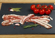 Raw bacon slices, spice and tomato on black board. Raw pork bacon slices, rashers, spices, peppercorns, garlic, bay laurel leaves and red fresh cherry tomatoes Royalty Free Stock Photos